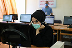 Palestinian graduates wearing a face mask as a preventive measure amid fears of the spread of the coronavirus disease (COVID-19), sit in a hall to solve employment exams to get a job, in Gaza city on, July 5, 2020. Photo by Mahmoud Ajjour
