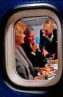 Air passengers having dinner, seen through window of plane