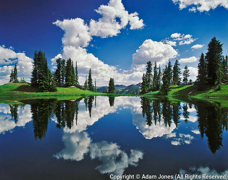 Alpine lake reflecting sky and clouds, Gunnison National Forest, Colorado