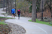 NWA Media/ J.T. Wampler - Glynn and Jennifer Bertrand of Bentonville walk on the Crystal Bridges trail at Compton Gardens in Bentonville Monday Dec. 22, 2014 during a misty gray morning. The National Weather Service is calling for partly sunny weather Tuesday with a slight chance for snow Tuesday night.