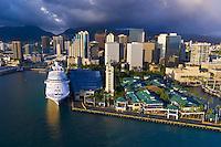 Princess Cruises' Regal Princess cruise ship docked next to the Aloha Tower and Aloha Tower Marketplace with Downtown Honolulu in back, Oahu, Hawaii, USA