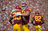 LOS ANGELES, CA - September 22, 2012:  USC offensive tackle Kevin Graf (77) congratulates running back Silas Redd (25) during the USC Trojans vs the Cal Bears at the Los Angeles Memorial Coliseum in Los Angeles, CA. Final score USC 27, Cal 9..