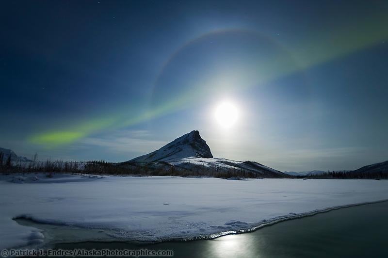 Streak of aurora borealis over Mount Sukakpak during a full moon night, Brooks range, Arctic, Alaska, Dietrich river
