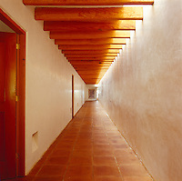 The beams of the ceiling echo the floor tiles in this long unfurnished corridor