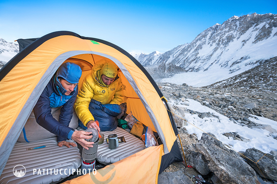 Ueli Steck and David Göttler cooking inside their advance basecamp tent during a climbing expedition to the 8000 meter peak Shishapangma, Tibet. Ueli is checking his watch.