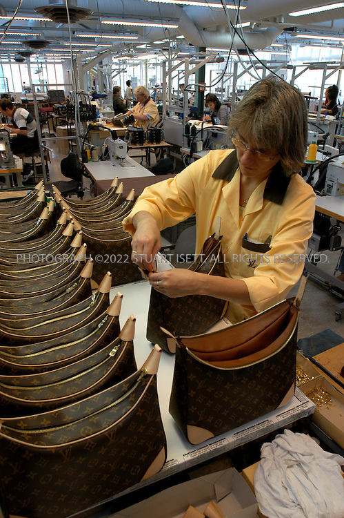 11/1/2003--Asnieres, France..Employees finishing a line LV handbags  at the factory and work shop. ..The Vuitton home, home to five generations of the family in Asnieres, 25 minutes from Paris. Today  it is a Museum, with an adjoining workshop where bags and trunks are still being made.In 1854, Louis Vuitton, the young trunk-maker founded the company Louis Vuitton in Paris, France after he enjoyed the ultimate honor of becoming Empress Eugenie's favorite specialist...All photographs ©2003 Stuart Isett.All rights reserved.This image may not be reproduced without expressed written permission from Stuart Isett.