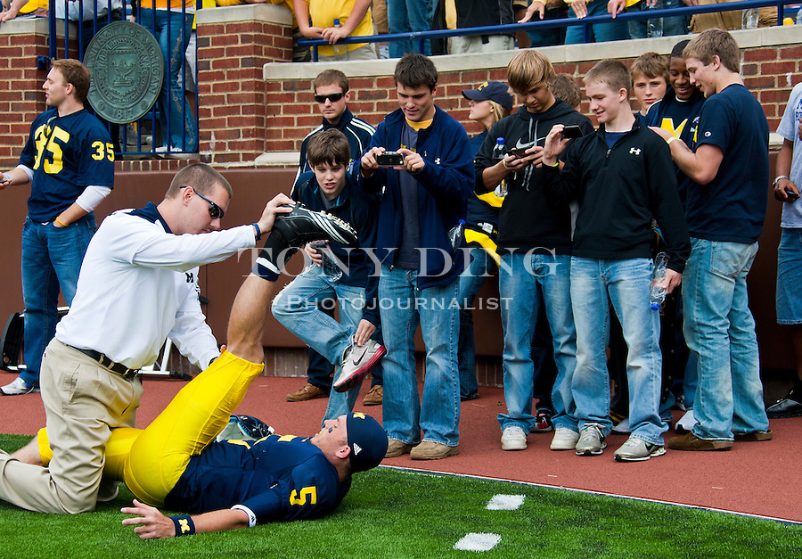 Michigan quarterback Tate Forcier (5) has some young fans recording him getting stretched on the Michigan Stadium turf, before an NCAA college football game with Connecticut, Saturday, Sept. 4, 2010, in Ann Arbor, Mich. (AP Photo/Tony Ding)