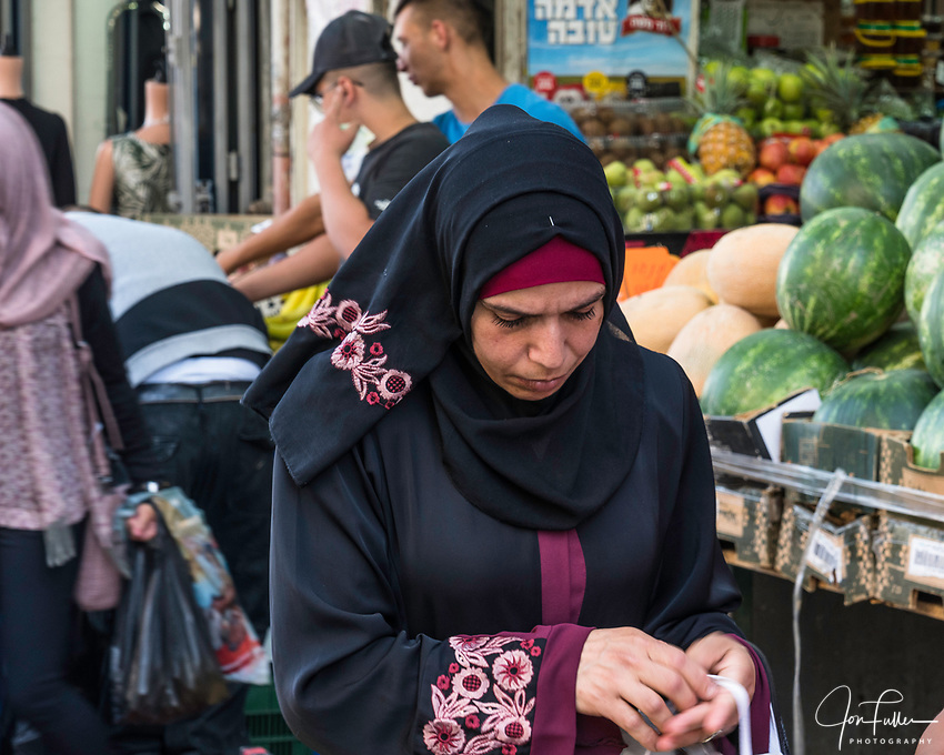 A Palestinian Arab woman wearing the traditional Muslim hajib or head scarf shopping for fresh produce on Nablus Street by the Damascus Gate in East Jerusalem.