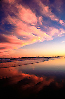 Stunning reflection of clouds on the low tide beach after a spectacular sunset on one of the beaches on the Northern Island of New Zealand.
