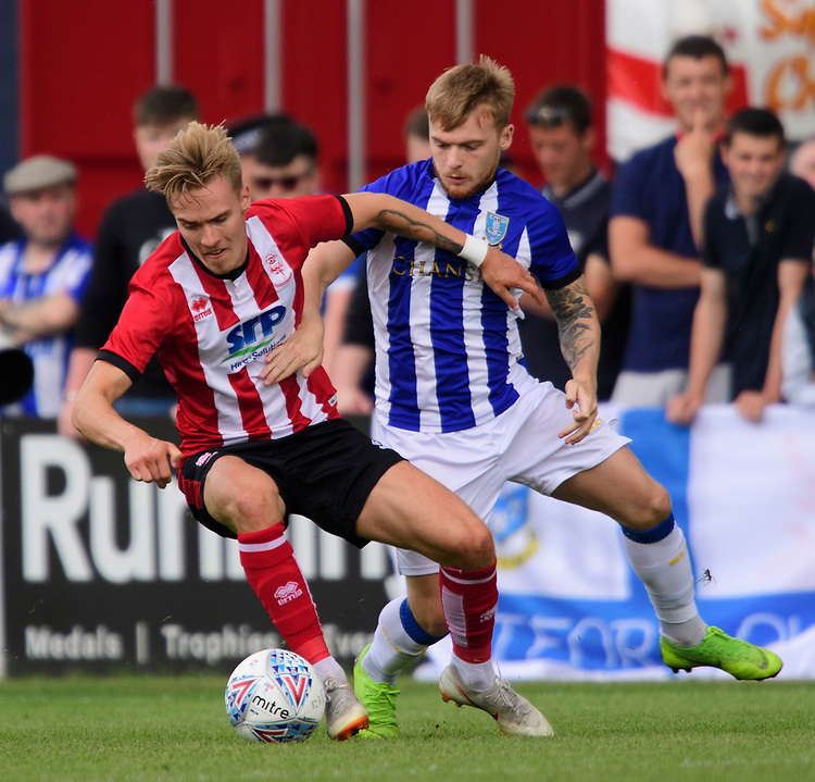 Lincoln City's trialist vies for possession with Sheffield Wednesday's Fraser Preston<br /> <br /> Photographer Chris Vaughan/CameraSport<br /> <br /> Football Pre-Season Friendly - Lincoln City v Sheffield Wednesday - Saturday July 13th 2019 - Sincil Bank - Lincoln<br /> <br /> World Copyright © 2019 CameraSport. All rights reserved. 43 Linden Ave. Countesthorpe. Leicester. England. LE8 5PG - Tel: +44 (0) 116 277 4147 - admin@camerasport.com - www.camerasport.com
