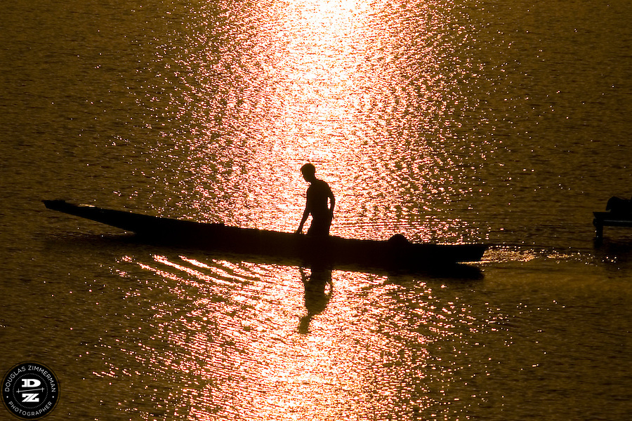 A fisherman guides his boat in Mekong river in Vientiane, Laos just before sunset. Photograph by Douglas ZImmerman.