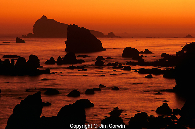 Sunset along Northern California coastline at sunset with silhouetted rock formations Crescent City California USA..