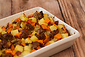 Roasted potatoes and carrots served with chunks of sausage in a white casserole dish