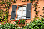 Window of a peach colored house with shudders, jasmine vines, and red flowers in Mandello del Lario, a town on Lake Como, Italy