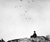 BNPS.co.uk (01202 558833)<br /> NARA/BNPS<br /> <br /> RAF Air Marshal Arthur Coningham sits in a Rhineland farmyard watching the Operation Varsity Allied air armada. <br /> <br /> Remarkable rarely seen photos of heroic Allied soldiers fighting their way across Europe before crossing the River Rhine 75 years ago feature in a new book.<br /> <br /> They are published in Images of War, Montgomery's Rhine Crossing, which tells the story of the legendary offensive, nicknamed Operation Plunder, in March 1945.<br /> <br /> On the night of March 23, Field Marshal Bernard Montgomery's 21st Army Group launched a massive artillery, amphibious and airborne assault to breach the historic defensive water barrier protecting northern Germany.<br /> <br /> At the same time, the Americans, with the support of the British 6th Airborne Division, set in motion Operation Varsity - involving 16,000 paratroopers - on the east bank of the Rhine. They were dropped here to seize bridges to prevent German reinforcements from contesting the bridgeheads.<br /> <br /> Fierce fighting ensued, with much bloodshed on both sides as the Allies met determined resistance from machine gun nests. But the daring operation proved successful, helping to considerably shorten the war - the Nazis surrendered just six weeks later.