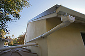 Drain pipes catch rain from metal roof for rainwater harvesting system on a Green home that is off the grid. Solar power and a rainwater harvesting system supply all the energy and water for this home in Los Angeles, California, USA