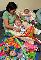 Infants in daycare setting with caregiver.