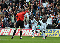 Pictured: Leroy Lita of Swansea (R) is shown a yellow card by referee Martin Atkinson after taking his shirt off while celebrating his goal. Saturday 17 September 2011<br /> Re: Premiership football Swansea City FC v West Bromwich Albion at the Liberty Stadium, south Wales.