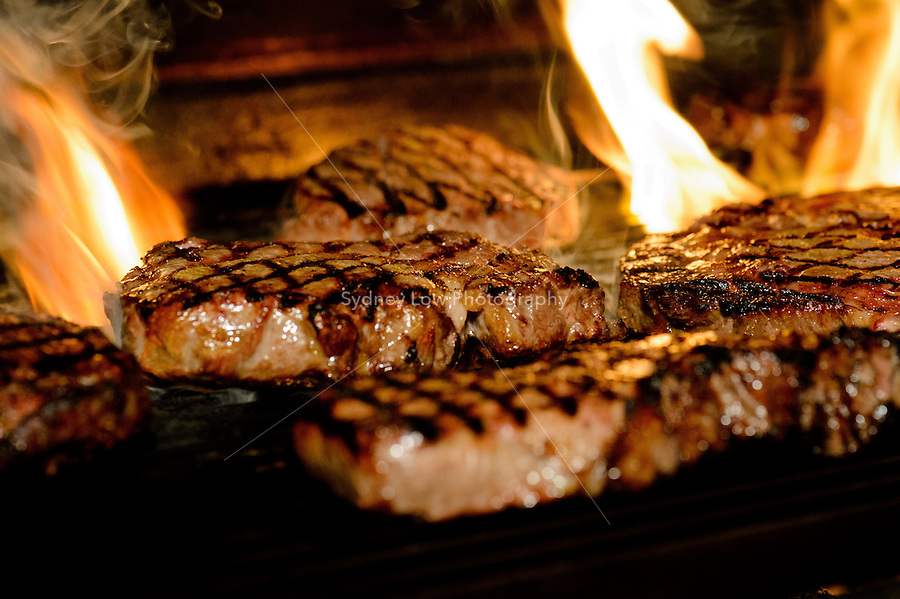 Sizzling steak on grill with flames