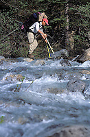CANADA, ALBERTA, KANANASKIS, MAY 2002. A hiker crosses Evan Thomas Creek. The Kananaskis Country provincial park is home to Canada's most beautiful nature and wildlife. It has also escaped the mass tourism as in Banff National Park. Photo by Frits Meyst/Adventure4ever.com