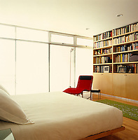 A red B&B Italia recliner is placed against a wall of books in one of the bedrooms