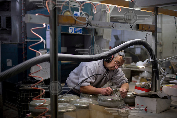A worker engraves one of the curling stones, produced from Ailsa Craig granite, at Kay's in Mauchline, Faslane. The company uses the same rock to make the stones that will be used at the Sochi Olympic Games.