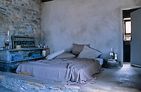 A bed on the raised sleeping area is flanked by shelving made of stone and slate