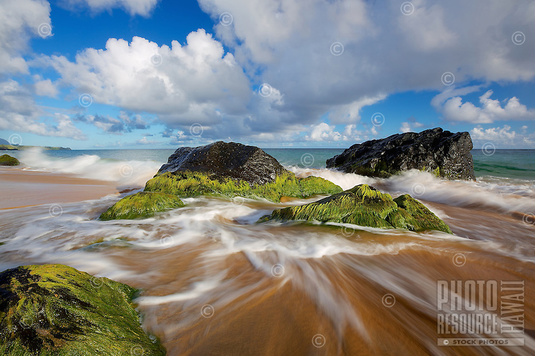 Waves rush onto mocha-colored sand and move in between green and black volcanic rocks under a big sky of clouds and blue, Secrets Beach, Kaua'i.