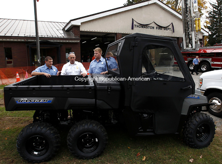 Thomaston, CT- 13 October 2013-101313CM10-   Captain John Albrecht, of the Thomaston Fire Department talks about their new 2014 Polaris, Ranger 800 6x6 All Terrain Vehicle to firefighters, John Maturo, left, and T.J. Quinn during an open house at the department Sunday.  The new vehicle, which was acquired through grants by Thomaston Savings Bank and the Department of Energy and Environmental Protection will serve as a multi-utility vehicle.  It will be able to transport personal and injured parties to and from otherwise inaccessible locations.  Capt. Albrecht said they vehicle can be outfitted with various types emergency equipment and will serve as a valuable asset to the department. Christopher Massa Republican-American