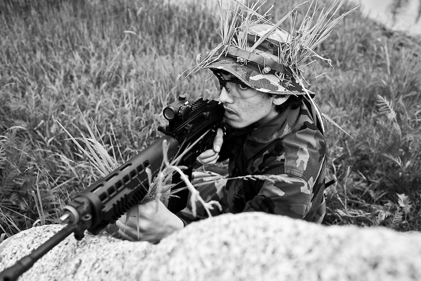 Charlie, a 16-year-old member of the Idaho Light Foot Militia from Couer d'Alene peeks over a rock looking for a mock enemy during a field exercise at a weekend-long training session at a camp near Priest Lake, Idaho.