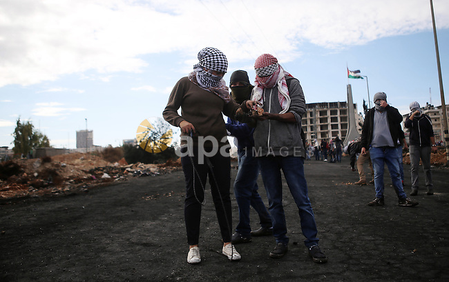 A female Palestinian protester uses a sling shot to hurl stones at Israeli troops during clashes near the Jewish settlement of Bet El, near the West Bank city of Ramallah, October 29, 2015. Israeli security forces shot dead two Palestinian assailants in the occupied West Bank on Thursday, police and the army said, as a month-long spate of stabbing attacks showed no signs of abating. Photo by Shadi Hatem