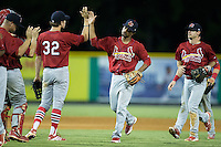 Eliezer Alvarez (center) high fives teammate Hunter Newman (32) following their victory over the Burlington Royals at Burlington Athletic Park on August 22, 2015 in Burlington, North Carolina.  The Cardinals defeated the Royals 9-3. (Brian Westerholt/Four Seam Images)
