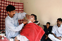 Man visits barber shop in village of Pattika, Pakistan