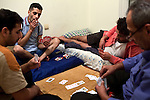 Khaled takes a drag on a cigarette while he, Mustafa, Abu Abed, and Muhammad play cards after the evening meal in their apartment in Athens, Greece, Oct. 13, 2014.