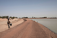 KOLONGO, MALI - FEBRUARY 24: A girl walks past some ruins where houses were destroyed to make way for a channel that was built by Chinese for Libyan company that leases land from the Mali government on February 24 2011, outside Kolongo, Mali. Photo by Per-Anders Pettersson