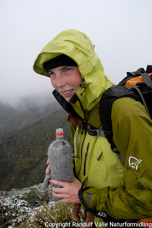 Jente har isolert drikkeflaska med en ullvott ---- Girl with water bottle insulated with mitten