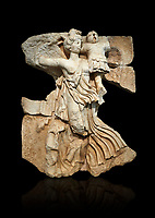 Roman Sebasteion relief  sculpture of the goddess Victory, Aphrodisias Museum, Aphrodisias, Turkey.   Against a black background.<br /> <br /> A winged goddess Victory( Nike) flies past carrying a military trophy. She wears a long light dress and has one breast and one leg exposed. Her clothing is set in motion by her swift flight.