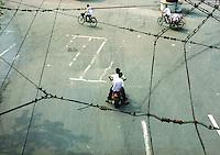 Cina, traffico su due ruote visto dall'alto in mezzo a fili elettrici di bus