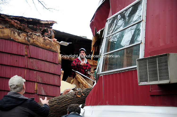 NEW MILFORD, CT, 30 OCT 12-103012AJ07-Leonard Belcourt tosses a wireless internet router to Ken Boehm Tuesday morning, while helping the Bertram family collect their belongings out of their home that was crushed by a fallen oak tree during Hurricane Sandy Monday evening.  Alec Johnson/ Republican-American