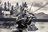 USA, Alaska, Homer, China Poot Bay, Kachemak Bay, one of the employees playing the violin on the dock at Kachemak Bay Wilderness Lodge, (B&W)