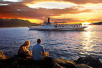 Youg couple watching a ferry at sunset on Lac Leman (lake Geneva) - Montraux Switzerland