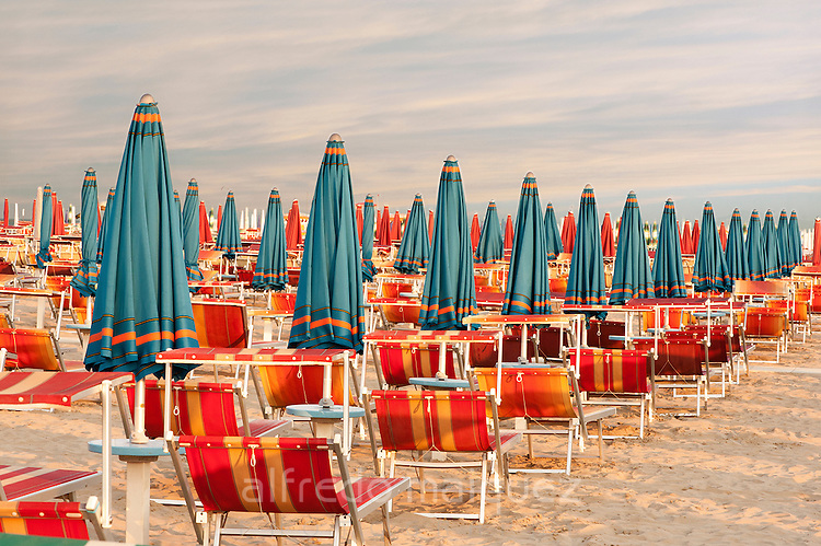 Withdrawn blue umbrellas and red sunlongers on the sandy beach in Italy