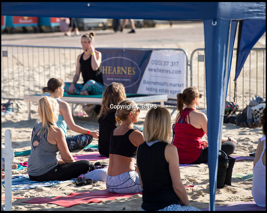 BNPS.co.uk (01202 558833)<br /> Pic: PhilYeomans/BNPS<br /> <br /> Sand sculpture...<br /> <br /> Flexible festival goers took to flat-karma seas today for Britain's first ever beach yoga festival.<br /> <br /> Under cloudless blue skies and bright sunshine, 'yogis' on stand up paddle boards took 30 minute classes on the crystal clear sea as Britain finally experienced a break in the wet weather.<br /> <br /> The inaugral three day Beach Yoga Fest is taking place on Bournemouth beach in Dorset involving classes on land and sea over the weekend.