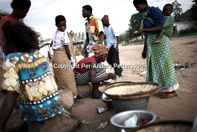 GALUFU, MALAWI NOVEMBER 15: Women sell fried fish along the road on November 15, 2005 in Galufu, Malawi. Most people in the village are poor and hungry, and cannot afford to buy maize or other food at the market. The price is twice as much as the government subsidized prices. The government used to sell subsidized maize and fertilizer but not anymore. Many in the village eat mangoes and even boil unripe ones, as they cannot afford to buy anything else. The harvest was very bad in 2005 and the next one, due in April 2006 I uncertain because of lack of rains and drought. The village has seen an increase in poverty the last few years due to drought and HIV/Aids. Southern Africa has been hit by a severe hunger crisis due to drought and poverty. An ever-increasing HIV/Aids rate adds to the misery. Malawi is one of the worst hit areas and Galufu village is a typical small village that has become victim of this poverty spiral. (Photo by Per-Anders Pettersson)
