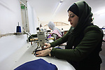 Amina Hamo, 25, a Palestinian fashion designer works on dresses at her shop on the occasion of International Women's Day, in Gaza city, on March 8, 2018. International Women's Day is annually held on March 8 to celebrate women's achievements throughout history and across nations. It is also known as the United Nations (UN) Day for Women's Rights and International Peace. Photo by Mahmoud Ajour