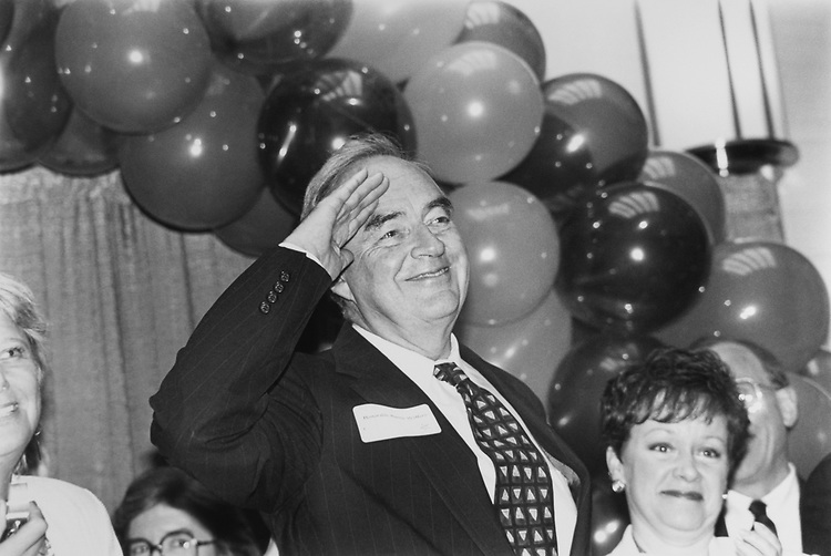 Women's Campaign Fund reception at NEA building. Sen. Harris Wofford, D-Pa., salutes to the audience as he is introduced. Rep. Jill Long Thompson, D-Ind., also attended the event on May 20, 1993. (Photo by Maureen Keating/CQ Roll Call via Getty Images)