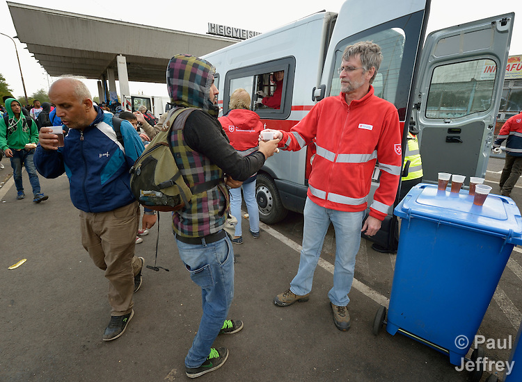 Gabor Kovacs, a volunteer with Malteser International, a Catholic organization, gives coffee to migrants and refugees as they pass through the Hungarian town of Hegyeshalom and prepare to cross the border into Austria. Hundreds of thousands of refugees and migrants flowed through Hungary in 2015, on their way to western Europe from Syria, Iraq and other countries. Malteser International is the relief agency of the Sovereign Order of Malta.