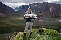 June 30, 2011, Ron Karpilo holding a photograph taken in the same location in 1919 by U.S. Geological Survey geologist Stephen R. Capps, East Fork Toklat Valley, Denali National Park and Preserve, Alaska, United States.