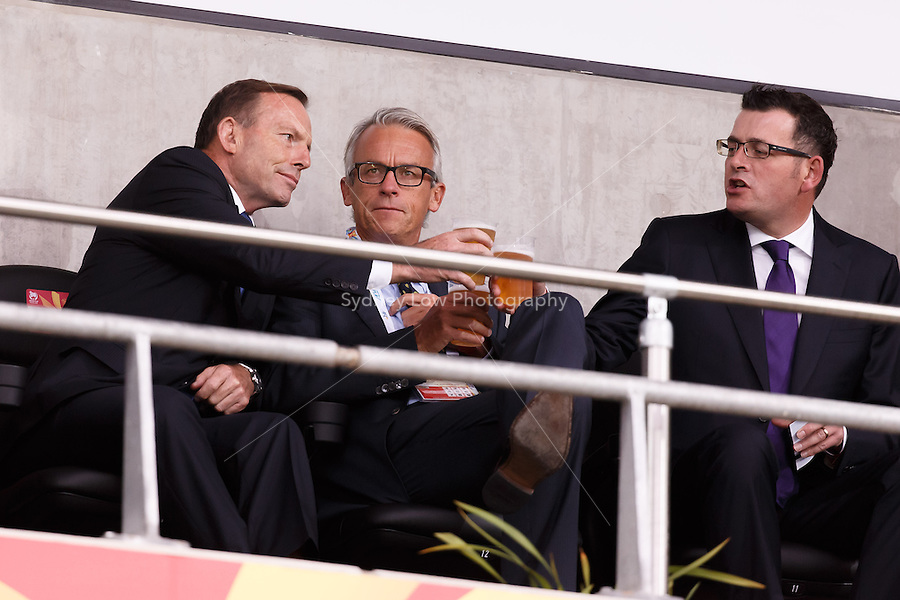 The Australian Prime Minister Tony Abbott shares a drink with David Gallop the CEO of the Football Federation Australia and Daniel Andrews the premier of Victoria at the 2015 AFC Asian Cup match between Australia and Kuwait at the Melbourne Rectangular Stadium on 9 January 2015