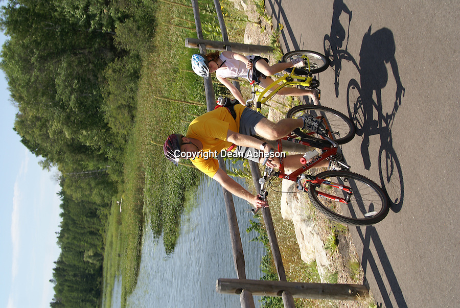 A pair of bicyclists pass by a lake in Vilas County. The northern Wisconsin bike trail is paved and popular with summer tourists.